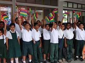 Education in Mauritius and Finance - Children raising the colourful Mauritian flag at school.